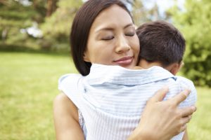 Pretty young Asian mother hugging her little boy in a park